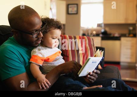 Père lecture pour bébé sur canapé Banque D'Images