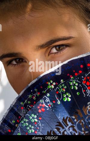 Un joli visage de filles cachée par un fan espagnol traditionnel. Banque D'Images