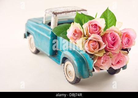 Vieux camion transportant des jouets anciens fleurs rose rose Banque D'Images