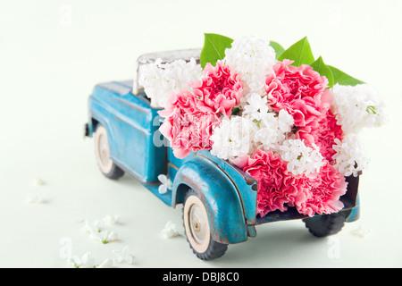 Ancien jouet ancien camion transportant des fleurs lilas et oeillet rose Banque D'Images