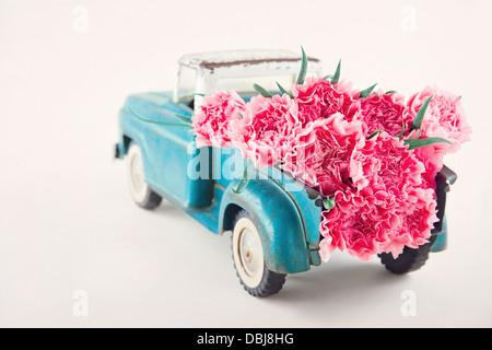 Vieux camion transportant des jouets anciens fleurs oeillet rose Banque D'Images