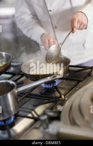 Cuisiner dans une cuisine commerciale Banque D'Images