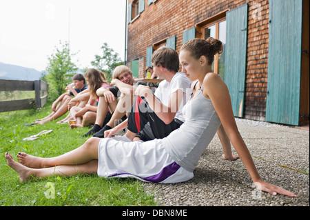 Les adolescents se détendre devant une maison, Sonthofen, Schattwald, Bavière, Allemagne Banque D'Images