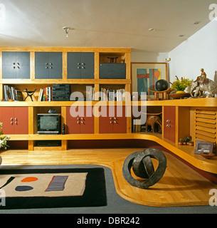 Tapis à motifs abstraits et plancher en bois pâle dans années 90 salon avec plancher au plafond équipé de l'unité Banque D'Images