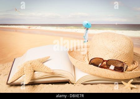 Chapeau de paille et lunettes de soleil couché sur le livre face à l'océan Banque D'Images