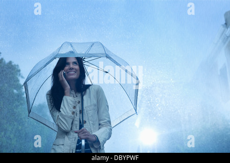 Businesswoman talking on cell phone under umbrella in rain Banque D'Images