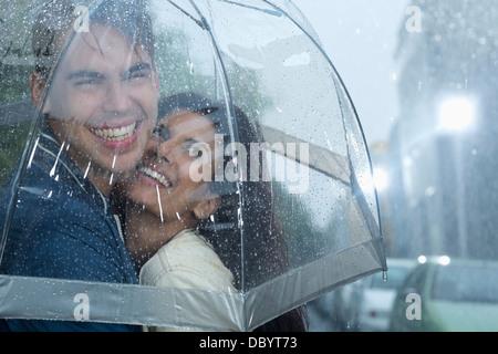 Heureux couple hugging under umbrella in rain Banque D'Images