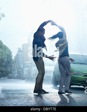 Heureux couple dancing in rain Banque D'Images