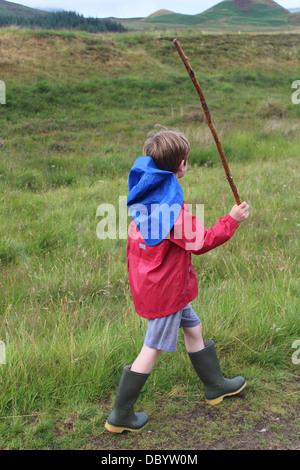 Garçon dans pluie balade dans les Highlands écossais Banque D'Images