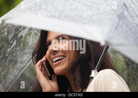 Happy woman under umbrella in rain Banque D'Images