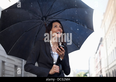 Happy businesswoman text messaging with cell phone under umbrella in rain Banque D'Images
