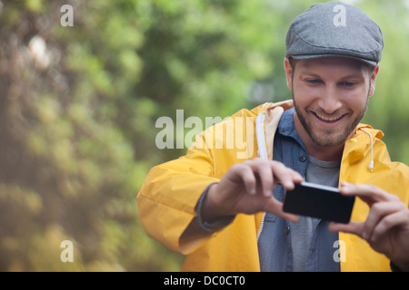 Happy man taking photograph with camera phone Banque D'Images