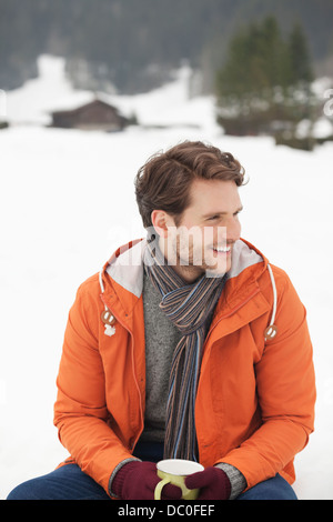 Smiling man drinking coffee in snowy field Banque D'Images