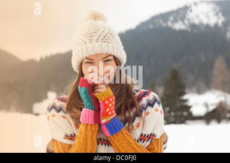 Portrait of smiling woman wearing Knit hat in snowy field Banque D'Images