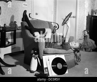 Années 1950 Années 1960 TEENAGE GIRL SMILING couchée à l'ENVERS SUR UNE CHAISE TENANT VINYL RECORD ALBUM À ÉCOUTER Banque D'Images