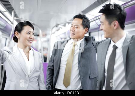 Les personnes d'affaires gaies dans Subway train Banque D'Images