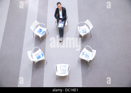 High angle portrait of smiling woman sitting at chair in circle Banque D'Images