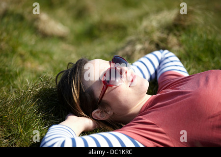 Jeune femme portant des lunettes de soleil en forme de coeur lying on grass Banque D'Images