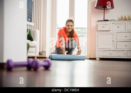 Jeune femme roulant tapis d'exercice à la maison Banque D'Images
