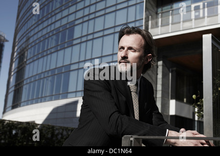 Mid adult businessman looking away in city Banque D'Images