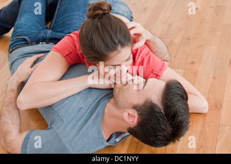 Jeune couple lying together sur plancher en bois Banque D'Images