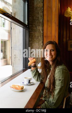 Jeune femme de manger un sandwich au café de Barcelone, Espagne Banque D'Images