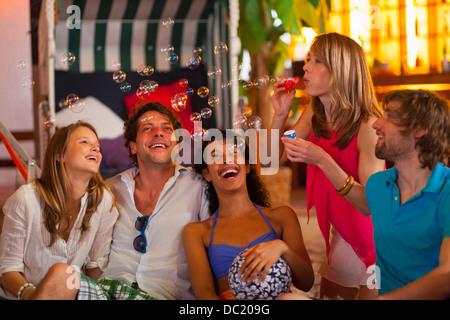 Groupe d'amis faisant des bulles à l'indoor beach party Banque D'Images