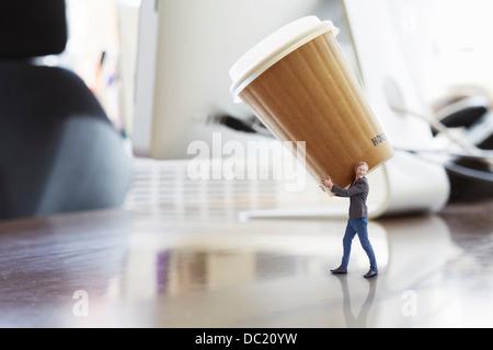 Mature businessman carrying large gobelet jetable sur un immense bureau Banque D'Images