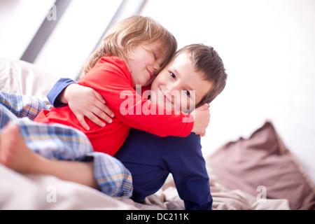 Deux jeunes enfants hugging on bed Banque D'Images