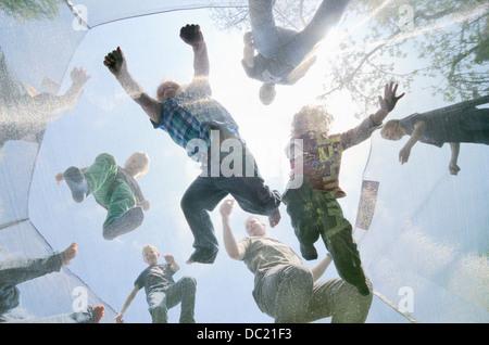 Les hommes et les garçons matures de sauter sur un trampoline, low angle view Banque D'Images