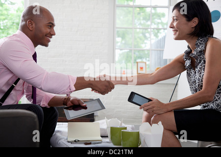 Office colleagues shaking hands in meeting, smiling Banque D'Images