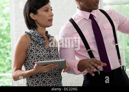 Collègue de bureau holding digital tablet in meeting Banque D'Images