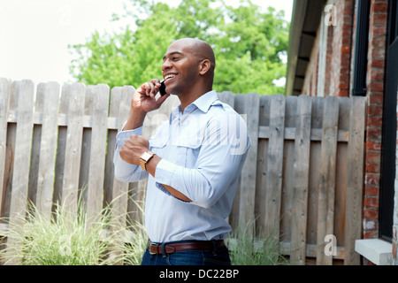 Mid adult man using mobile phone in garden, smiling Banque D'Images