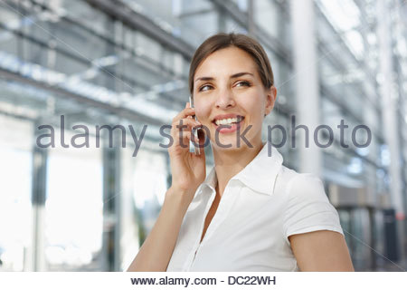 Young businesswoman using mobile phone, smiling Banque D'Images