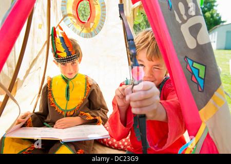Frères vêtus de costumes autochtones américaines jouant en tipi, portrait Banque D'Images