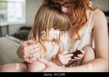 Mother and Daughter, using smartphone Banque D'Images