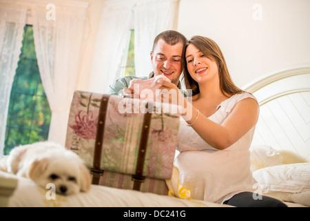 Couple à la recherche à travers des cas de vêtements de bébé Banque D'Images