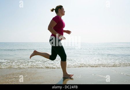 Woman running on beach Banque D'Images