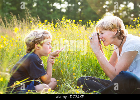 Woman taking photograph of boy blowing kiss Banque D'Images