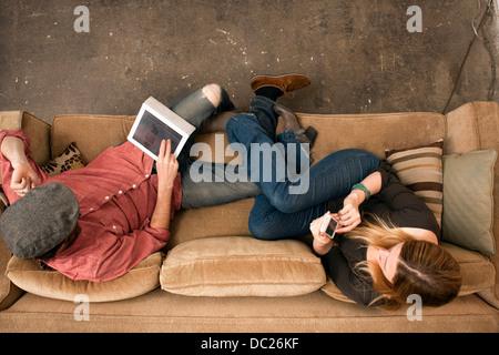 Couple sitting on sofa using digital tablet et smartphone Banque D'Images