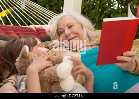 Grand-mère et petite-fille reading book in hammock Banque D'Images