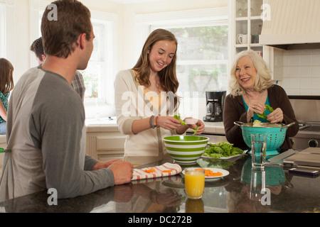 Petits-enfants avec grand-mère de préparer un repas dans la cuisine Banque D'Images