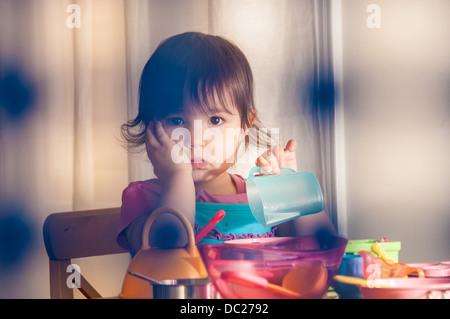 Triste fille jouant avec des jouets Banque D'Images