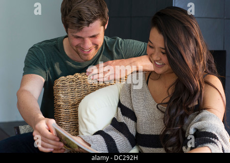 Young couple looking at magazine, smiling