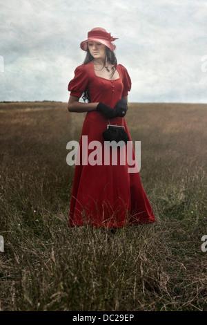 Une femme en robe rouge est debout sur un champ
