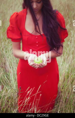 Une femme dans une robe rouge, tenant une pomme verte Banque D'Images