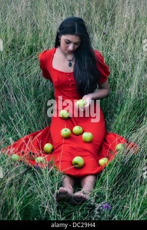 Une femme dans une robe rouge assise sur un champ, avec la pomme verte sur sa robe Banque D'Images