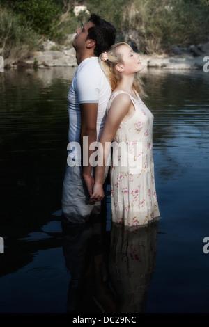 Un couple dans l'eau, dos à dos Banque D'Images