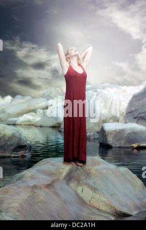 Une femme en robe rouge est debout sur un rocher dans l'eau et profiter du soleil