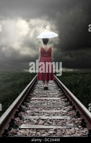Une fille dans une robe rouge avec un parasol est debout sur des rails de chemin de fer Banque D'Images